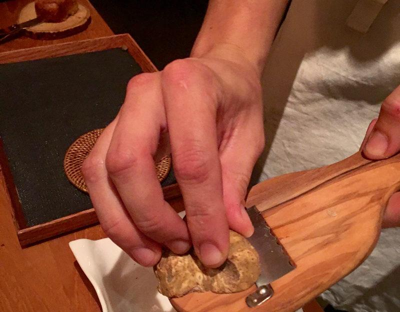 Shaving Wild white Alba truffles on matsutake mushrooms