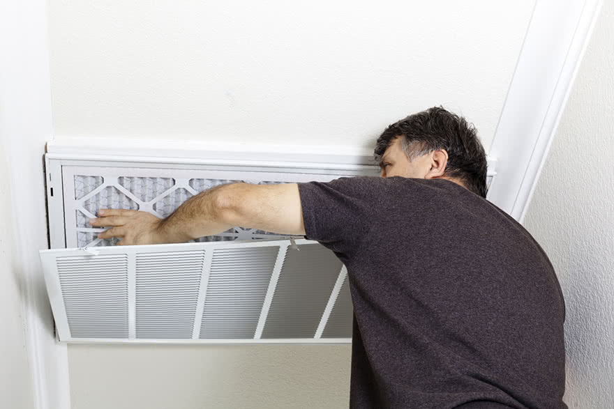 A man replacing the air filter on an HVAC system