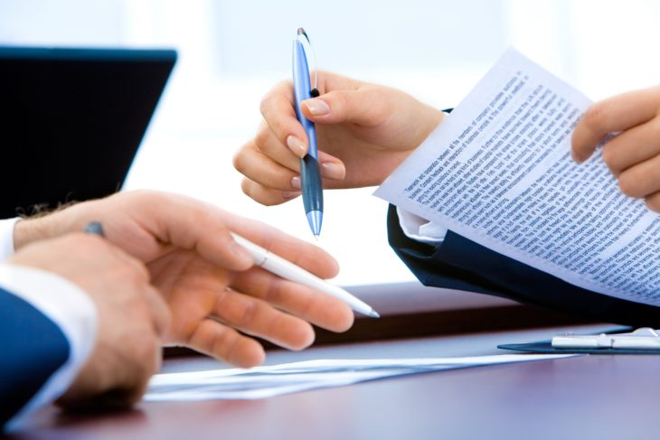 business hands holding pens and paper preparing to make a deal