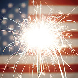 Lit sparkler burning in front of American Flag