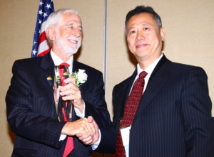 LIA's 2016 President Lin Li (right) presents Executive Director Peter Baker with the first LIA Leadership Award