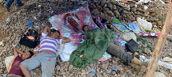 Las familias pasan rendidas debajo de champas improvisadas a la espera de noticias.