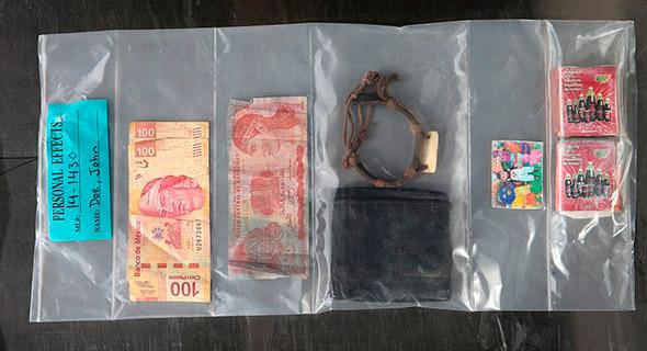 Monedas de Méxicoy Honduras, un brazalete y la fotografía de un niño están entre los artículos encontrados en éste cuerpo, recuperado del desierto de Arizona el 10 de junio 2014.