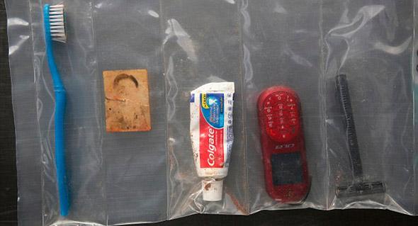 Una foto desteñida es preservada junto a artículos de tocador y un teléfono celular entre las pertenencias de uno de los muertos.