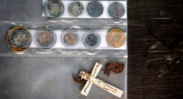 El crucifijo de un rosario roto y monedas que pertenecieron a una persona cuyos restos esqueléticos fueron encontrados en el desierto de Arizona, el 12 de septiembre del 2014.