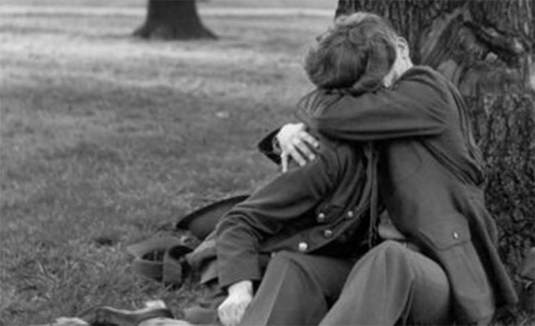 Una pareja de enamorados besándose en el parque. 1945.