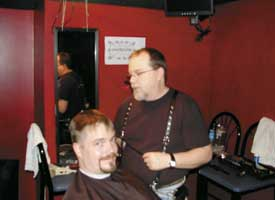 Leather barber Brian Preston gives John Warner a haircut.