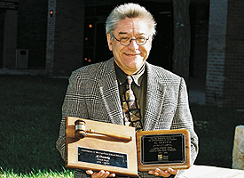 Al Oertwig holding awards for his service on the Association of Metropolitan School Districts (left) and the Council of Urban Boards of Education (right). Photo by Sophia Hantzes