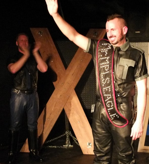Jason Little, the new Mr. Minneapolis Eagle 2014, waves to the crowd as his predecessor, Ryan Brown, watches from the wings. Photo by Steve Lenius.