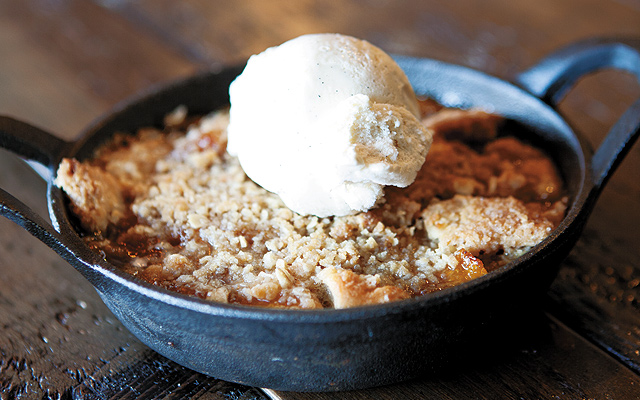 Peach cobbler with a drop-biscuit bottom, bourbon peach filling, and oatmeal streusel topping served with vanilla ice cream topped with bourbon sauce.