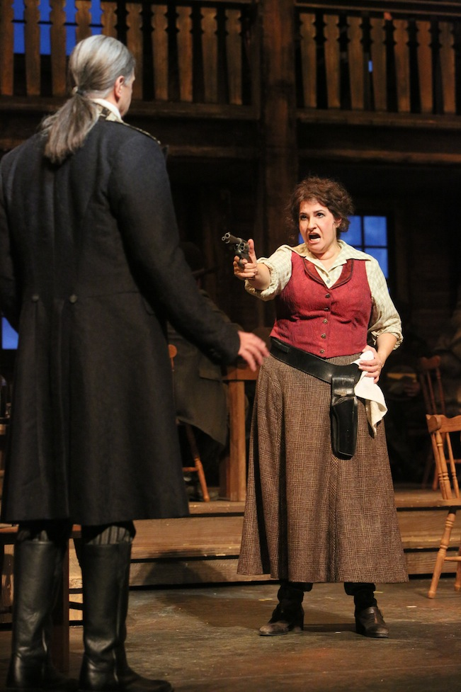 Claire Rutter (right) as Minnie points a gun at Sheriff Jack Rance (played by Greer Grimsley). Photo by Michal Daniel