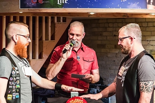As host/emcee David Coral (center) reads a question, Andrew Bertke (left) of the Atons of Minneapolis faces off at the buzzer with Randy Ingram-Lile (right) of Impawsters. Photo by Andrew Bertke.