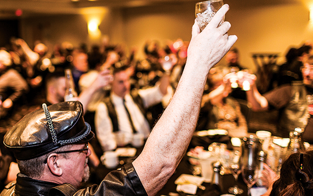 Knights of Leather banquet attendees raise their glasses in honor of the club's founding leatherwomen. Photo by Everett Allen Photography