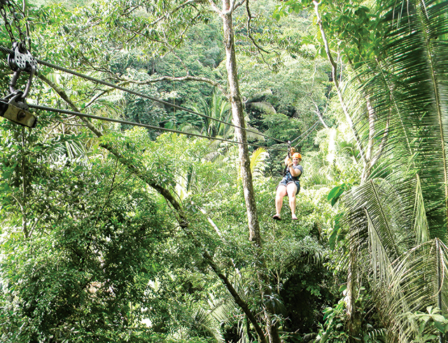 Kathleen rides a zip line through the jungle canopy. Photo by Krissy Bradbury