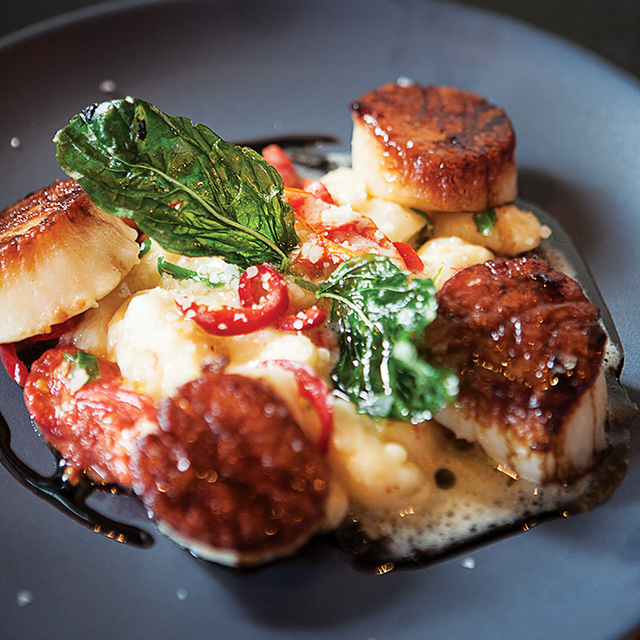 Dive into the cast-iron seared jumbo scallops with poached tomato, potato gnocchi, balsamic, beurre monte, and fresno peppers. Photo by Hubert Bonnet