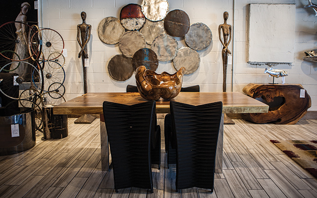 Statement Dining Table: Chamcha wood dining table ($5509), black seatbelt dining chairs ($659 each), skinny female sculpture ($1329), root bowl ($1209), galvanized circle tiles, various colors ($109 each), silver leaf circle tiles, set of 4 ($379). Photo by Mike Hnida