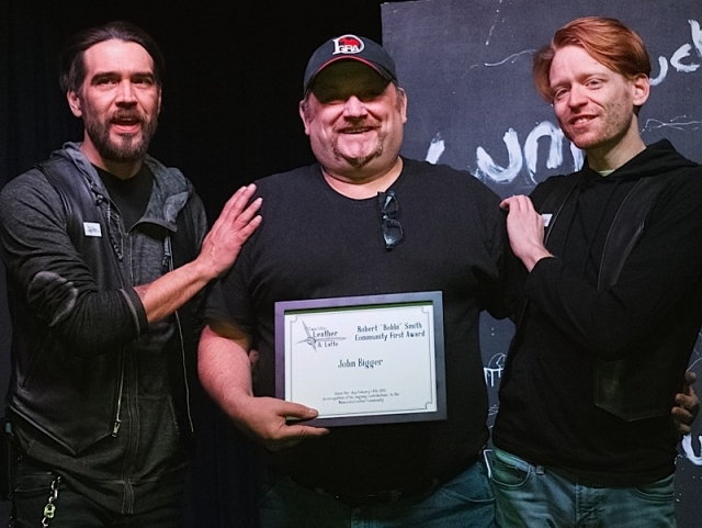 John Bigger (center), winner of the Robert Smith Community First Award presented by Twin Cities Leather & Latte, is congratulated by TCL&L co-owners Karri Plowman (left) and Tynan Fox (right). Photo by Steve Lenius.
