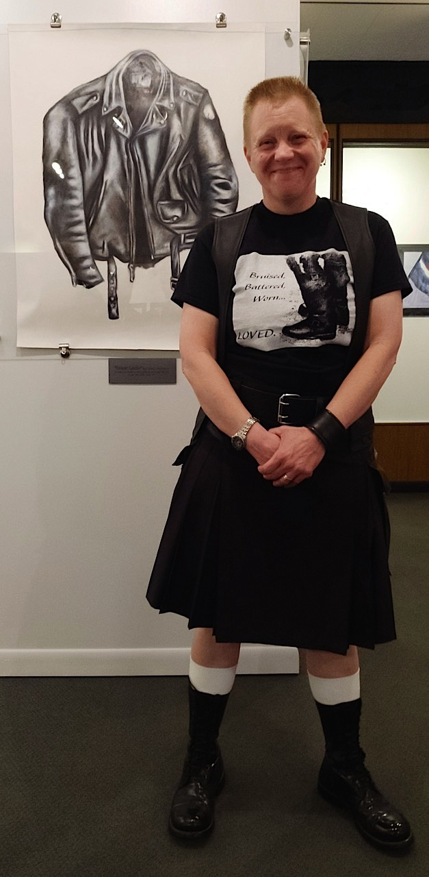 "Artist and bootblack Leslie J. Anderson stands in front of ""Forever Leather,"" a work of art that was created using boot and shoe polish. Anderson is wearing one of her limited-edition T-shirts. Photo by Steve Lenius."