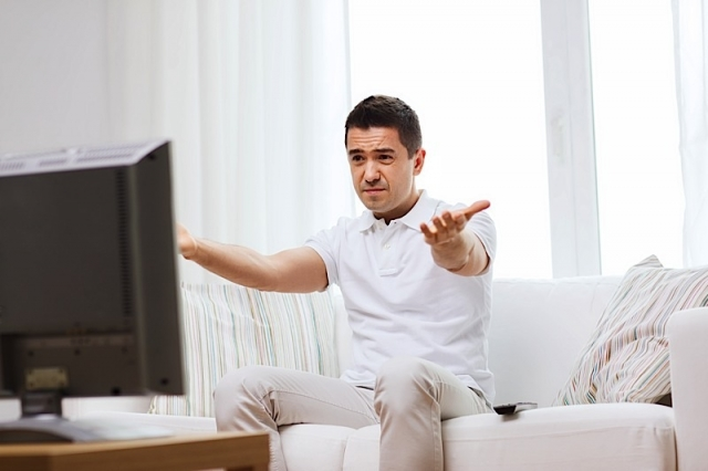home, people, technology and entertainment concept - disappointed man watching sports on tv and supporting team at home