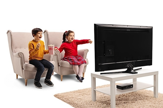 Happy little boy and girl sitting in an armchair watching TV and eating popcorn isolated on white background