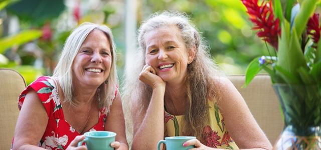 Beautiful pair of mature women sitting at table