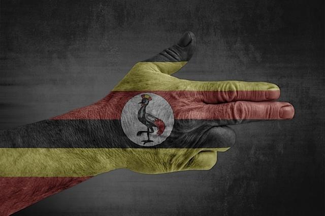 Uganda flag painted on male hand like a gun