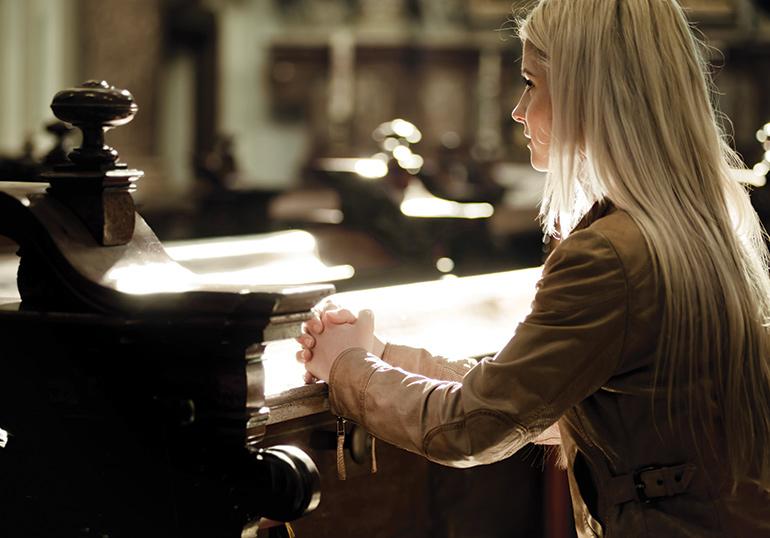 Jeune femme priant à l'église
