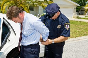 Man in tie being arrested 300x200