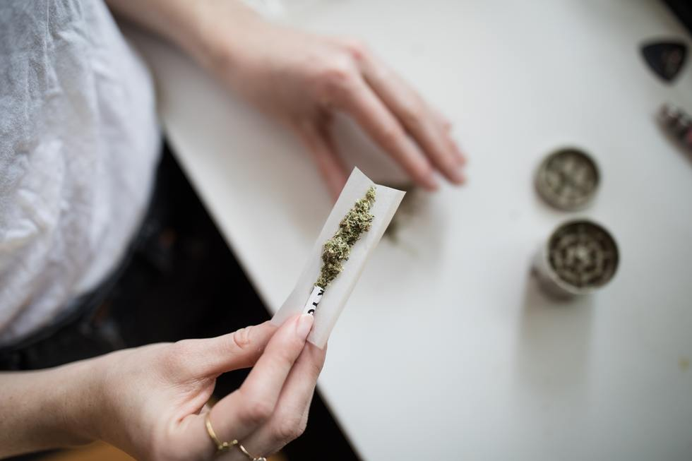 Woman rolling joint.