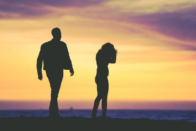 Silhouette of man and woman arguing on beach.