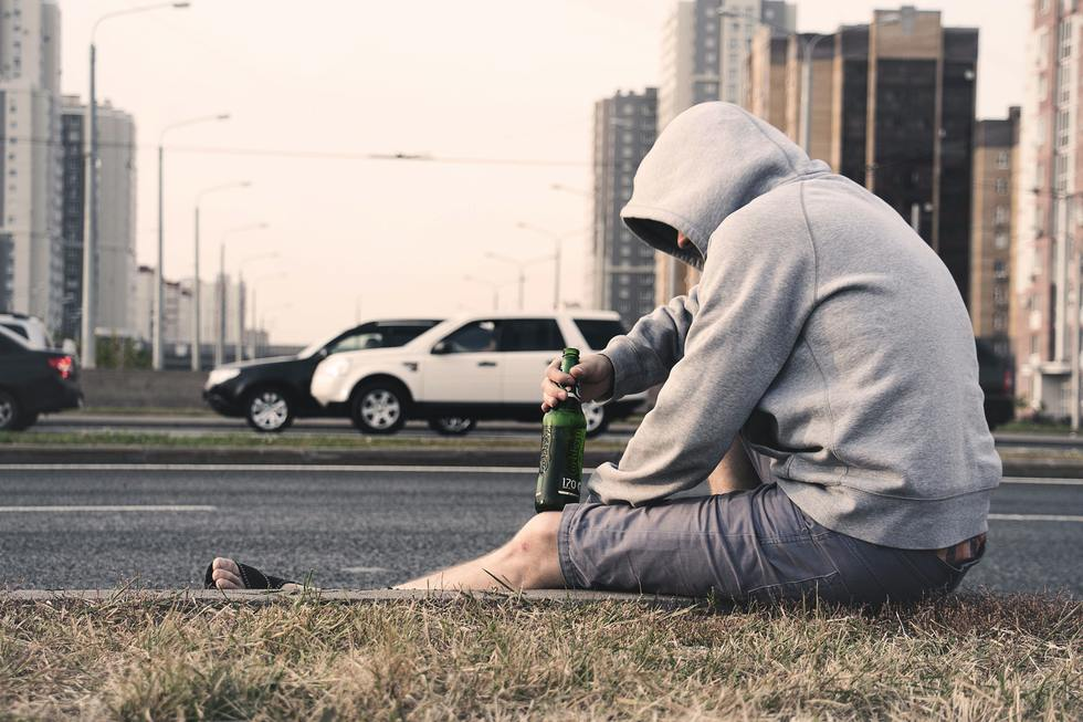 Man in grey hoodie drinks beer while sitting on a curb.