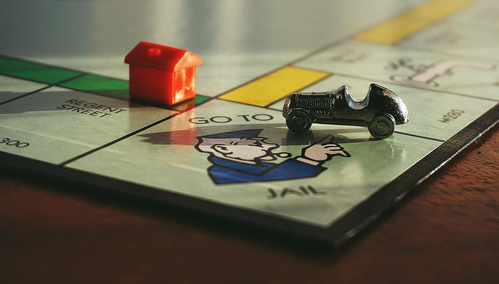 Monopoly game board with car piece on Go to Jail square.