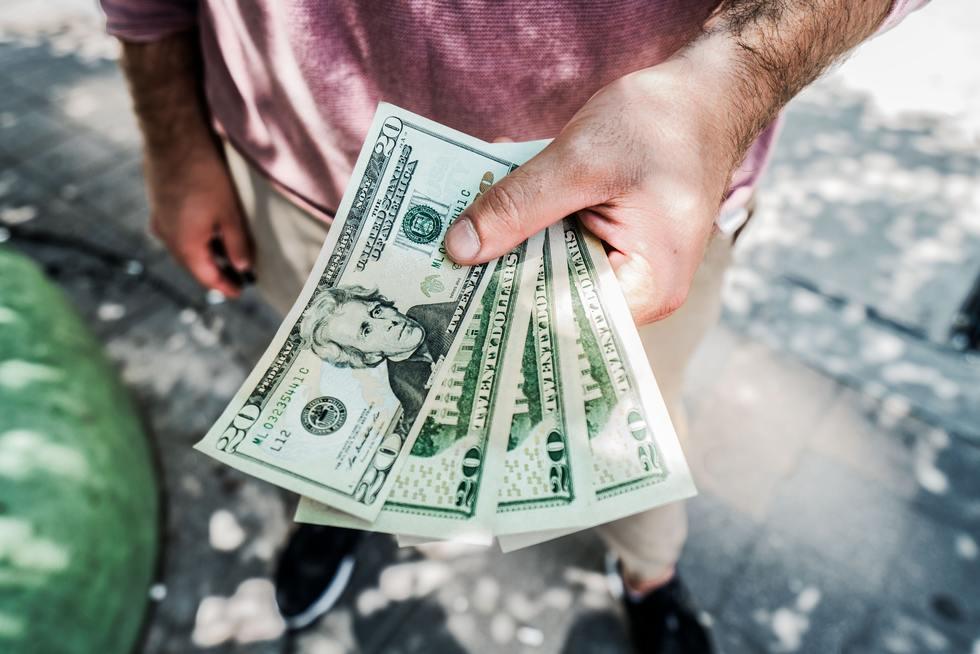 Man on street holding fan of 20 dollar bills.