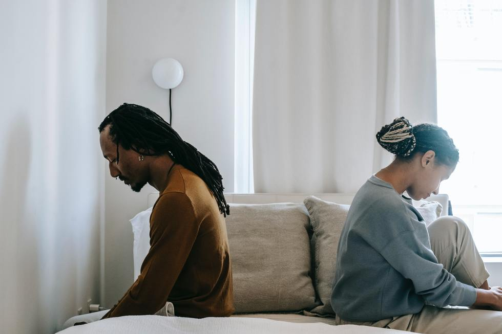 Black couple sit back to back on bed looking sad.