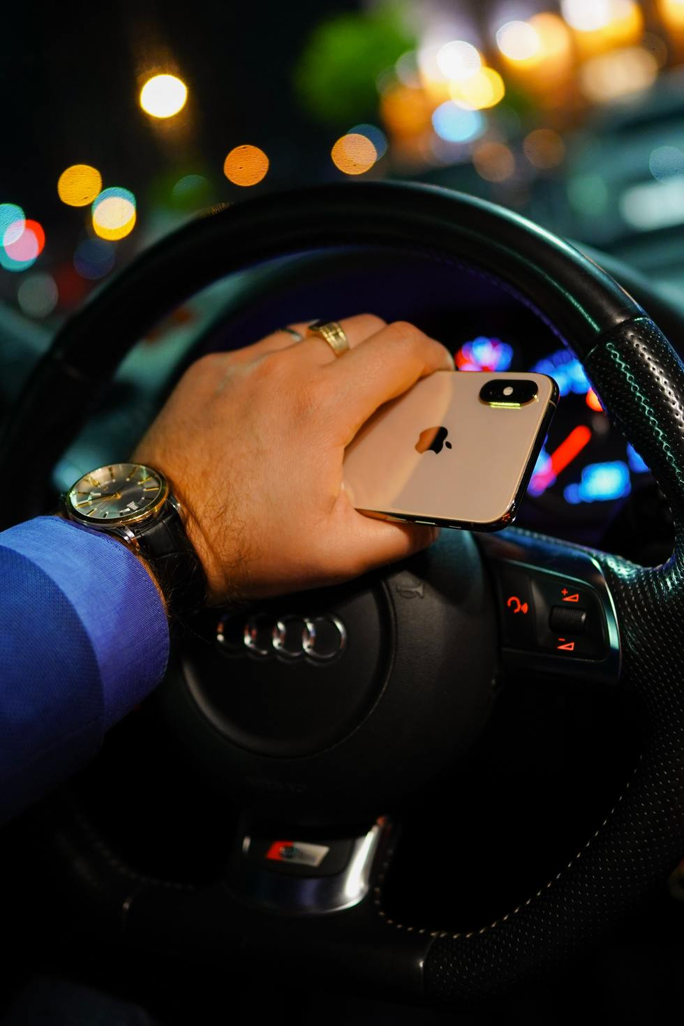 Man holds gold iPhone in hand on steering wheel.