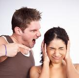 A man is yelling at a woman who is covering her ears to block him out.