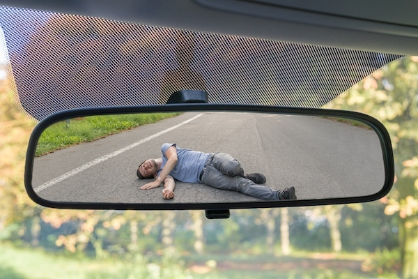 Reflection in visor mirror of a pedestrian hit by a car. The driver has the duty to stop and render aid under CRS 42-4-1603.