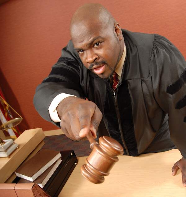 Judge with angry expression, holding gavel and pointing finger - contempt of court is a crime under Penal Code 166 PC