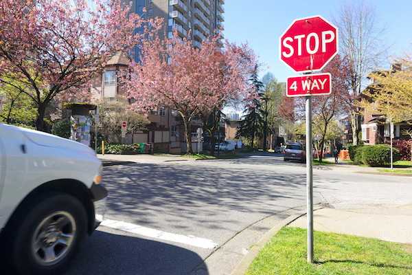 Car approaching a four-way stop intersection with a stop sign. Failing to stop violates Colorado law.