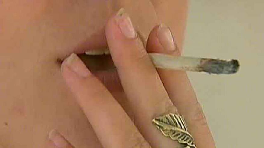 close-up of woman's hand holding a rolled joint to her mouth