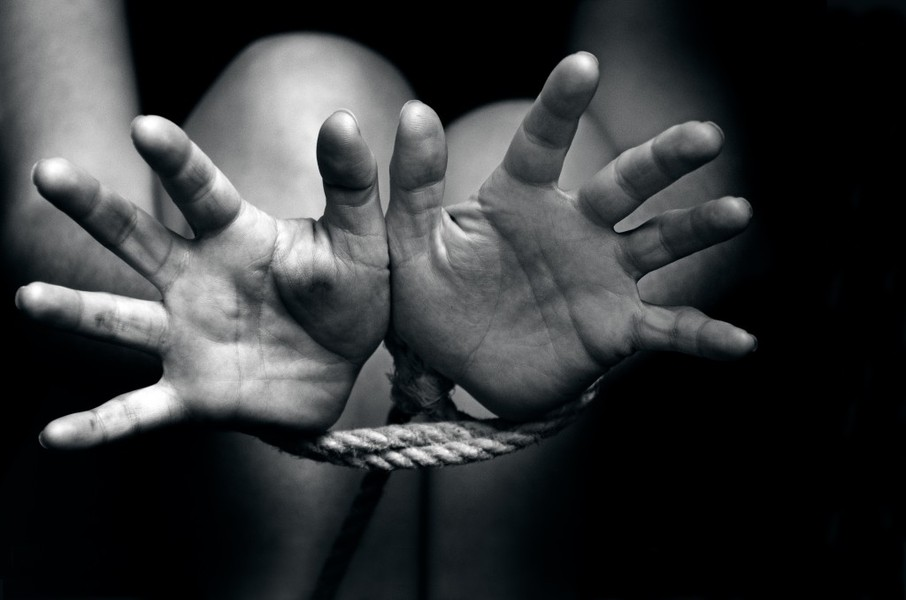 Woman's hands tied with ropes
