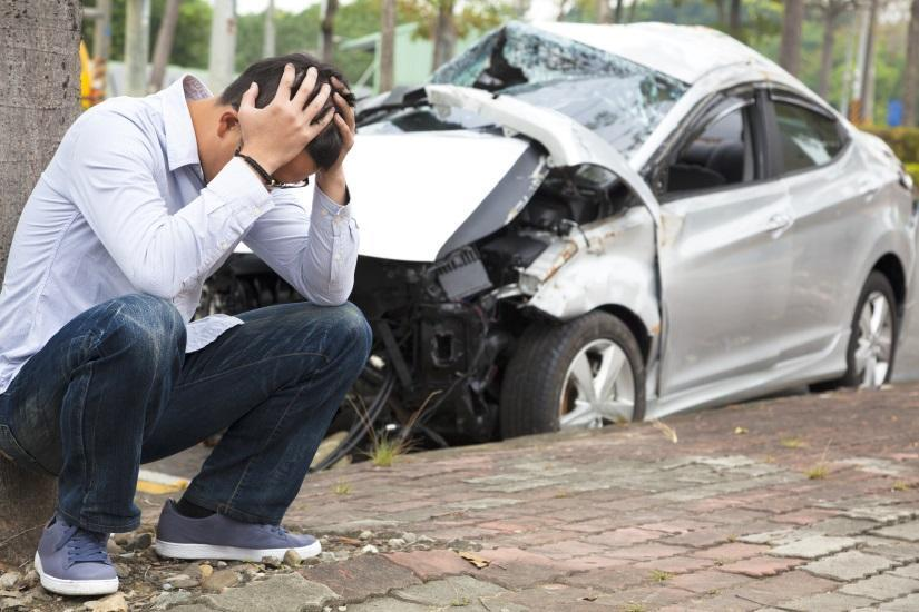 Man-with-head-in-hands-beside-wrecked-car