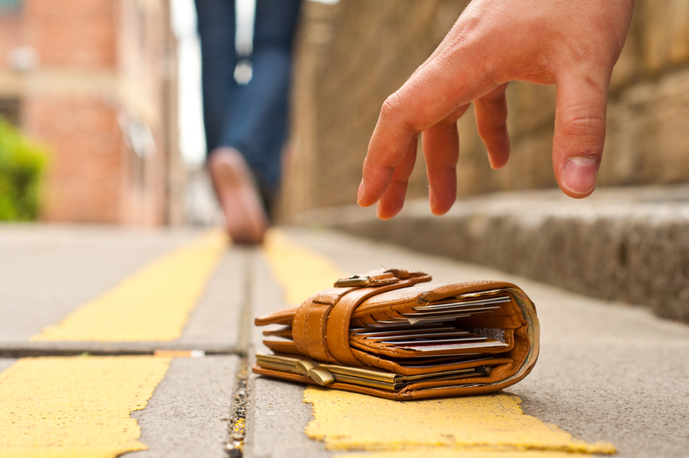 hand picking up dropped wallet from sidewalk
