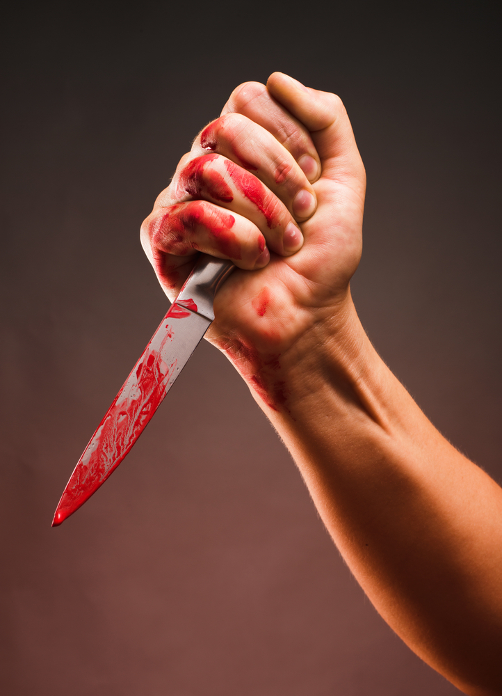 Hand holding bloody knife in stabbing position, indicating that the stabber has intent to kill under PC 664/187(a) - attempted murder