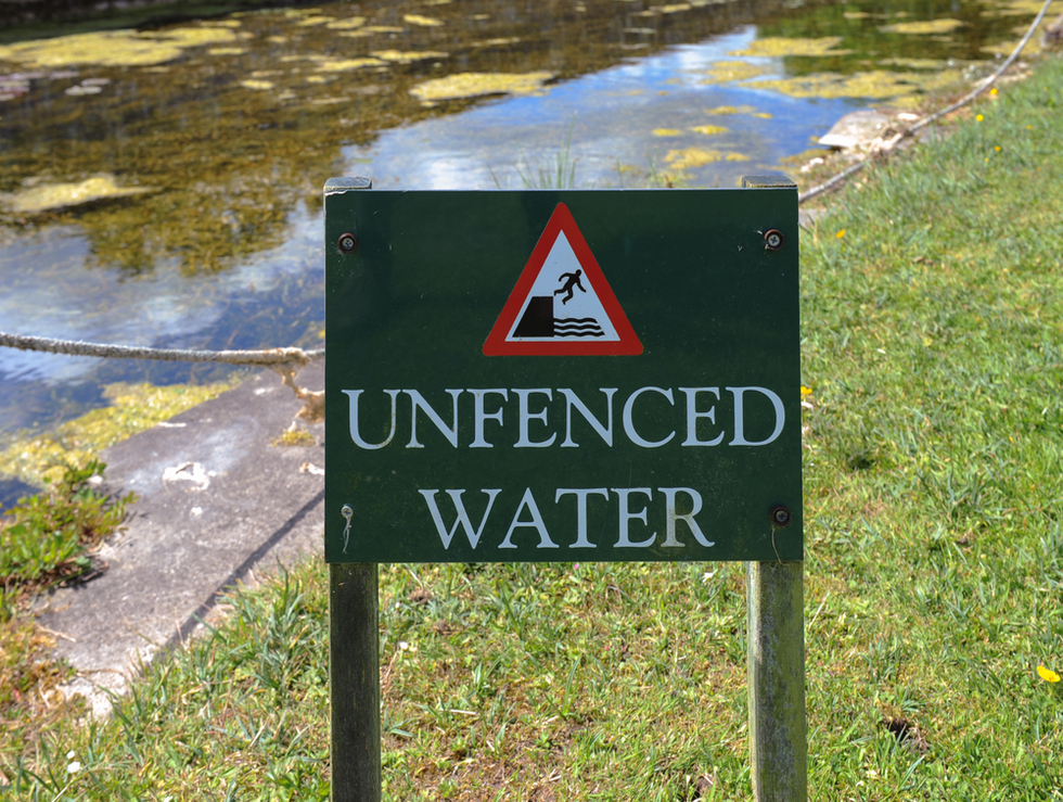 "sign reading ""unfenced water"" next to paved canal."