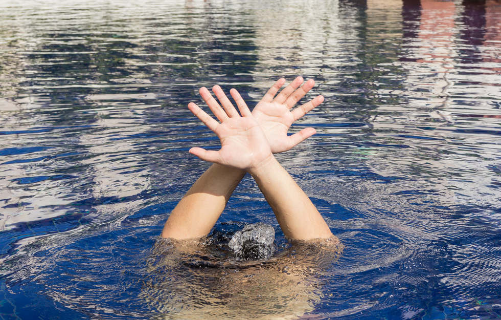 boy under water with hands breaking the surface, which could lead to a drowning and lawsuit