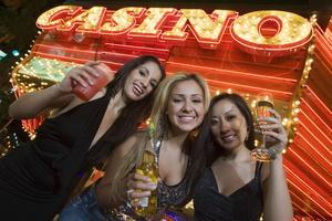 Three women holding drinks in front of a casino awning.