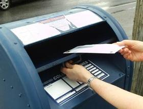 Hand-dropping-letter-in-mailbox