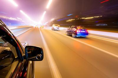 Car-speeding-on-highway-at-night