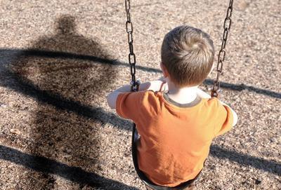 child sitting on a swing with an adult shadow next to him